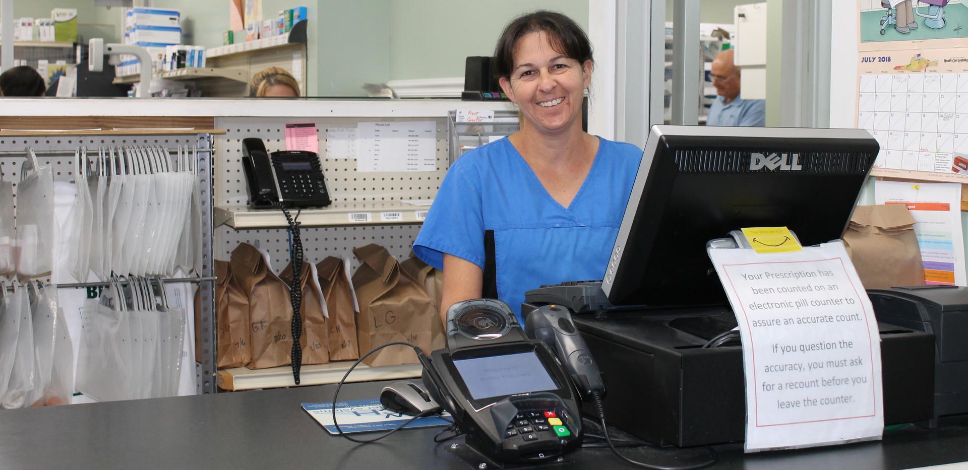 Wolfe's Pharmacy team member smiling at cash register