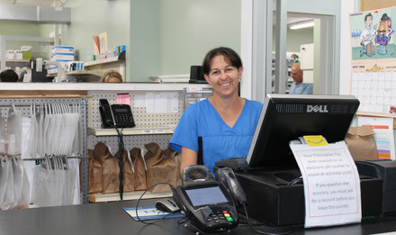 Wolfe's Pharmacy team member smiling at cash register