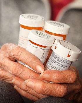 Hands holding prescription bottles