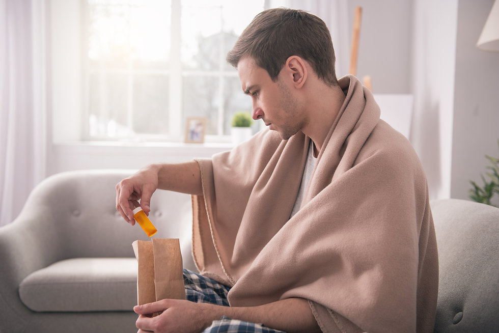 man sitting on couch looking at prescription