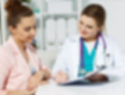 pharmcist talking with patient and pointing to clipboard