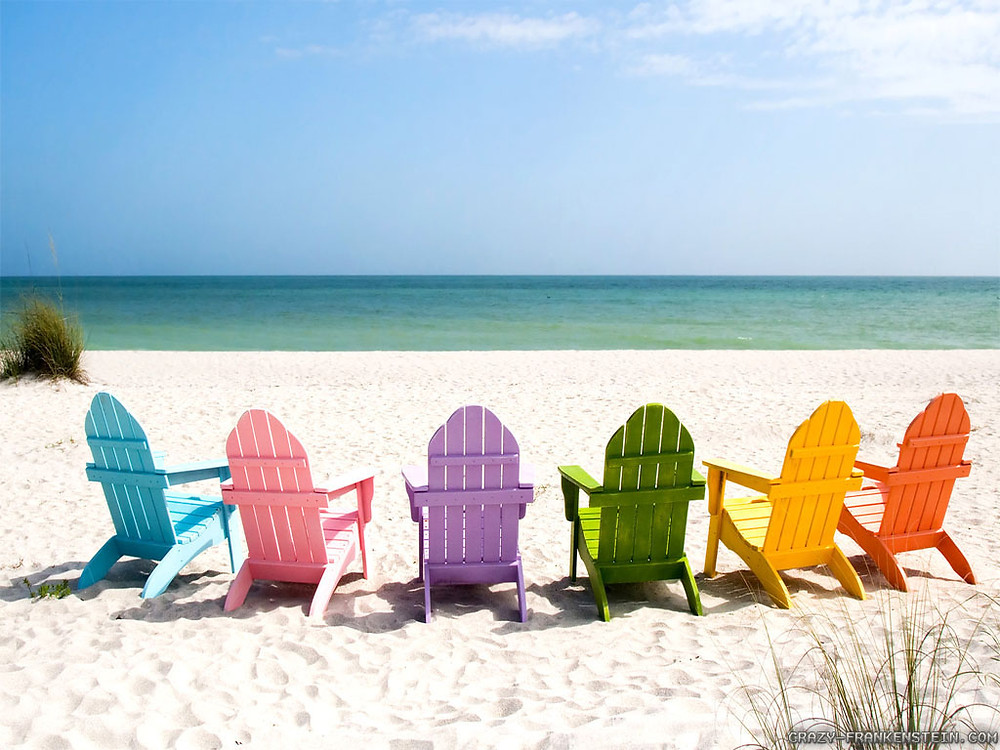 Multi color Adirondack chairs on the beach