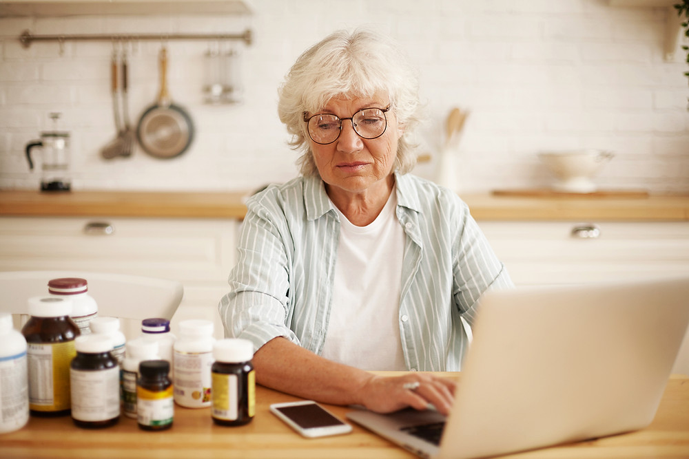 unhappy senior woman on computer with pill bottles