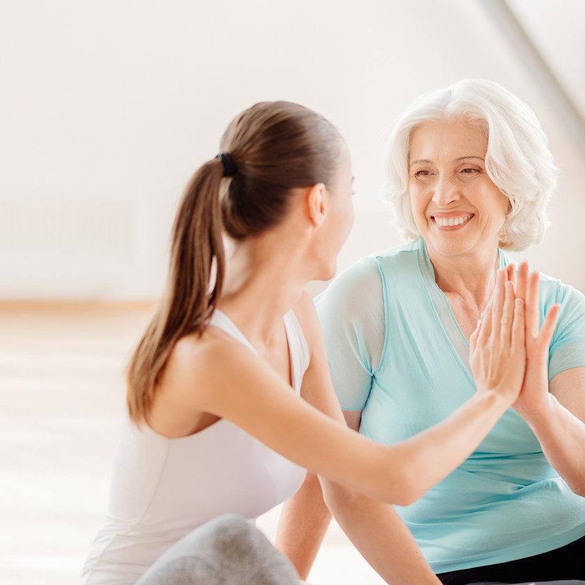 elderly woman working out with wellness coach