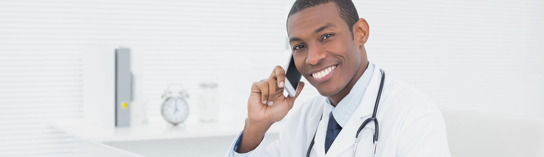 Male_Doctor_Smilling_Cell phone_Laptop.j