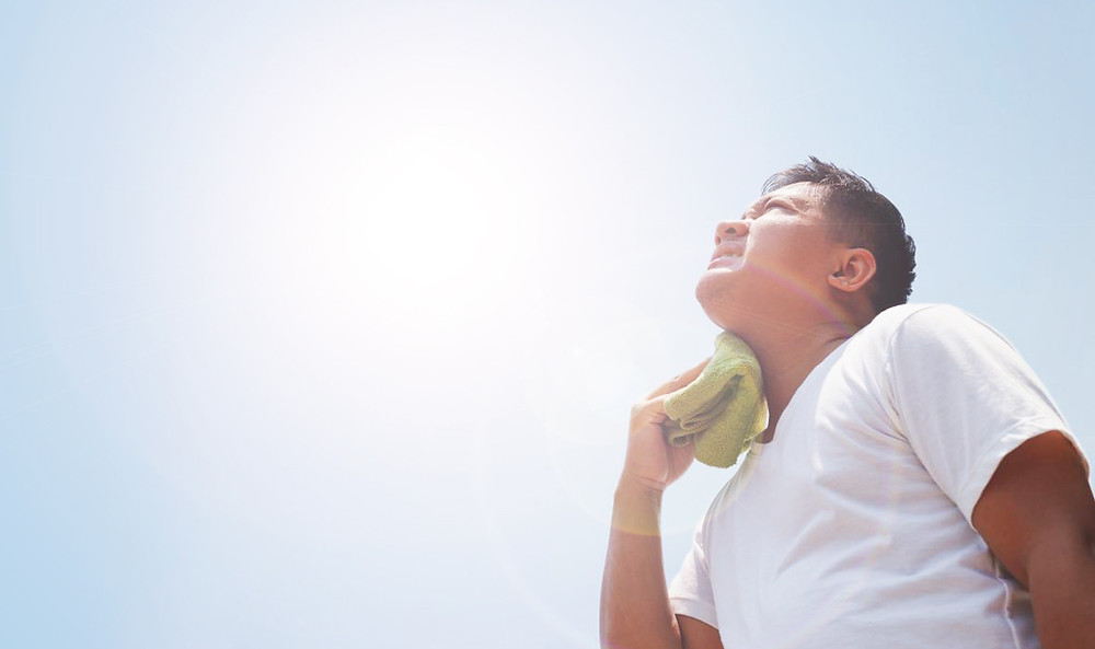 man looking up at the sun and wiping sweat