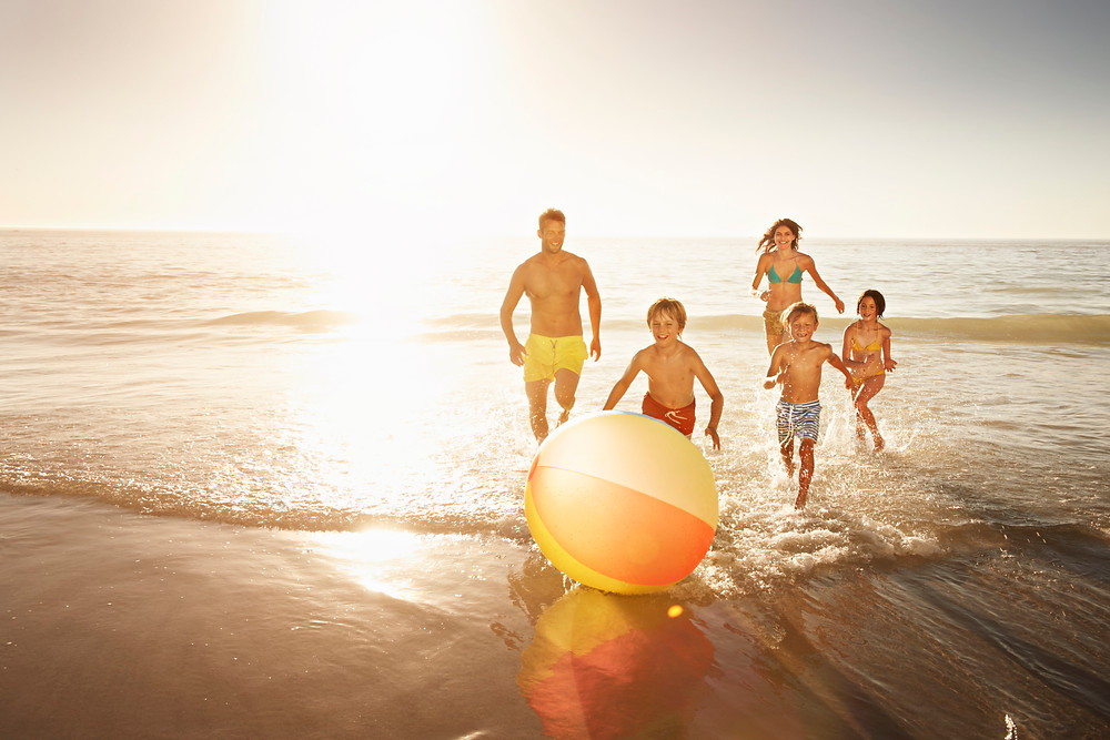 family playing with beach ball at sunset