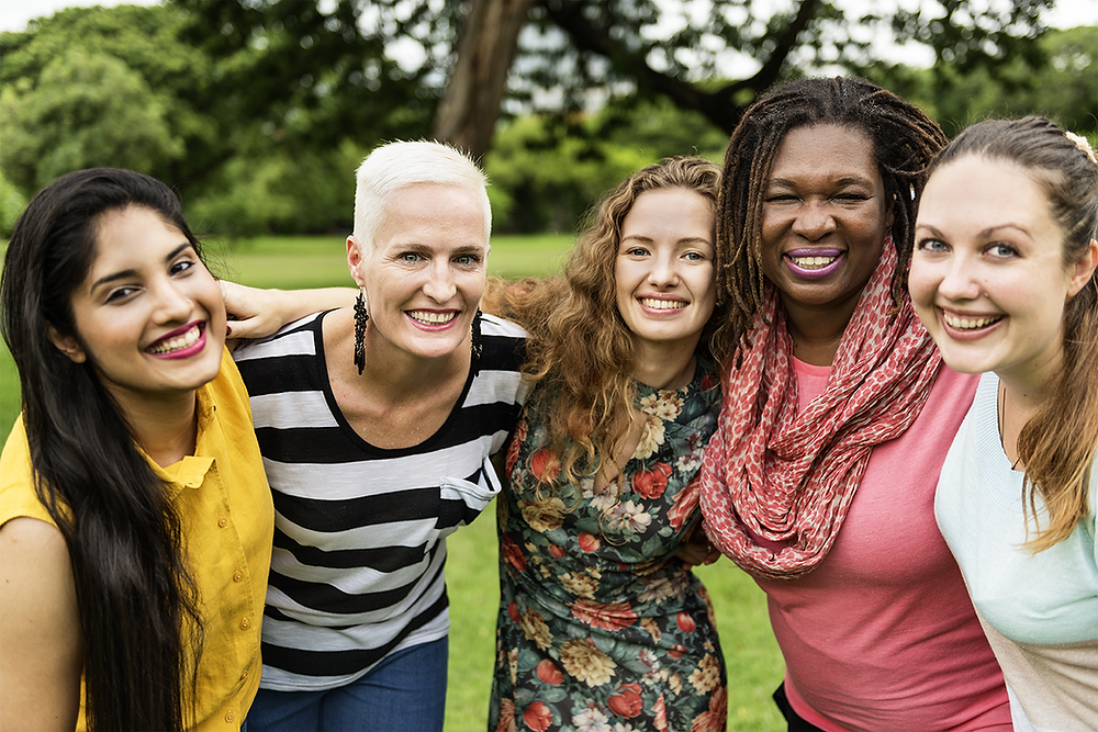 group of women embracing outside & smiling