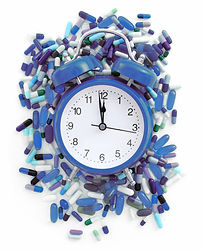 blue clock with blue pills scattered in the background