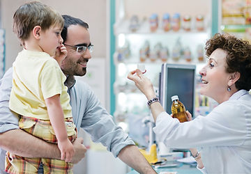 Pharmacist helping father and child