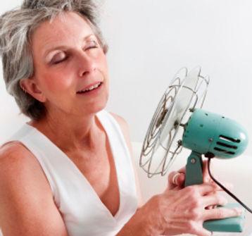 Woman having hot flash holding fan