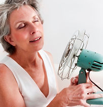 woman having hot flash holding fan