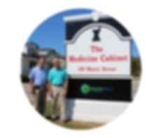 Terry Bushardt and Terry Blackmon pharmacy owners standing in front of The Medicie Cabinet pharmacy sign