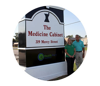 Terry and Erin Pharmacy Owners standing by Medicine Cabinet sign