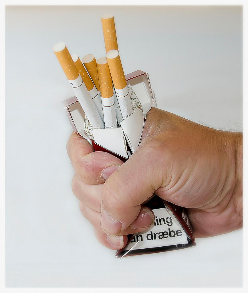 Hand crushing pack of cigarettes