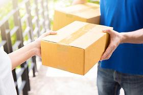 Hands delivering cardboard box