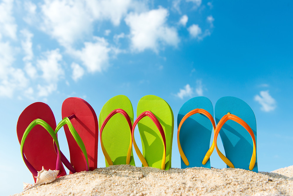 Multi-colored flip flops in the sand