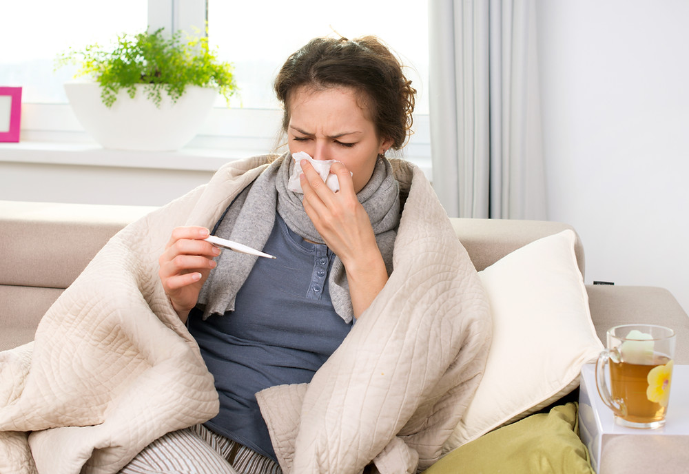 sick woman checking temperature and blowing nose