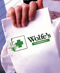 Wolfe's Phamacy delivery man holding up prescription bag