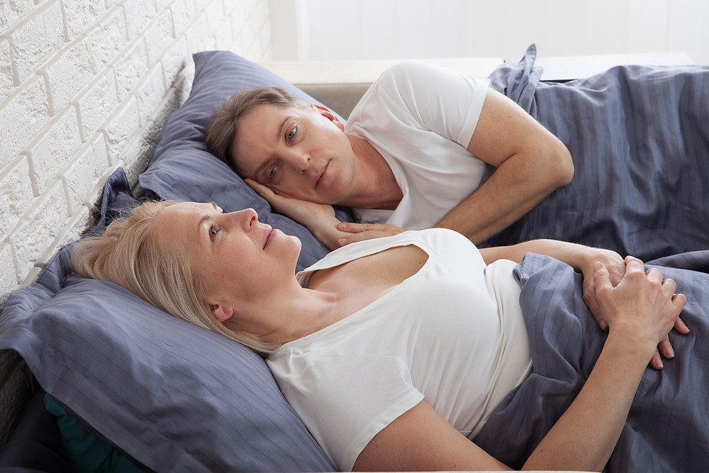 unhappy middle-aged couple laying in bed