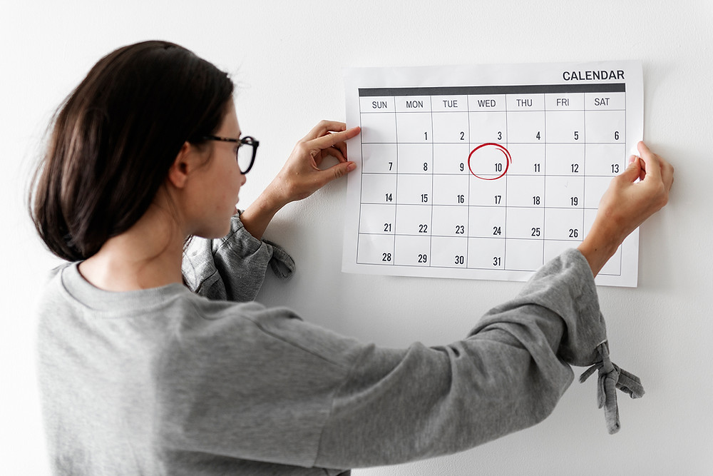 woman looking at calendar with date circled