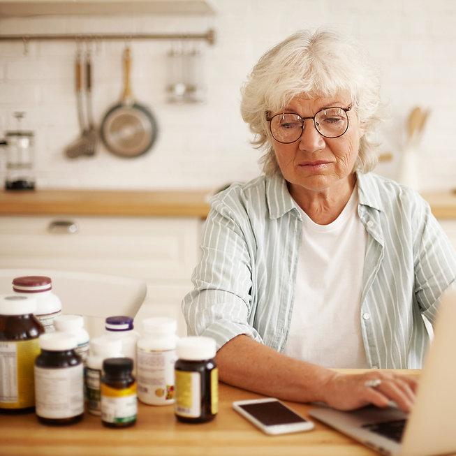 older woman looking at medication bottles