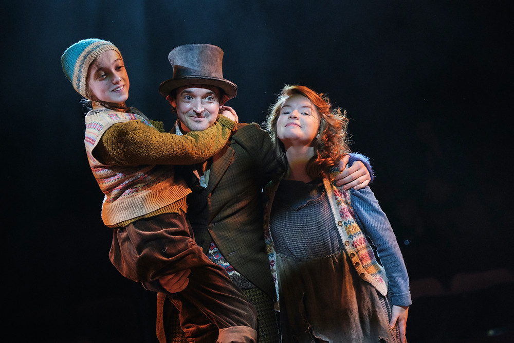 Niamh Moriarty as Tiny Tim, Hugh O'Conor as Bob Cratchit, and Catriona Ennis as Mrs. Cratchit in A Christmas Carol by Charles Dickens in a new version by Jack Thorne. Now at the Gate Theatre Dublin until 18 January. Photo by Ros Kavanagh.