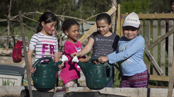 Young girls with watering cans at City Sprouts South