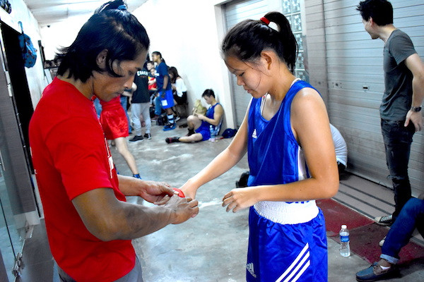 My boxing head coach Iskandar wrapping my hands for me before the fight.