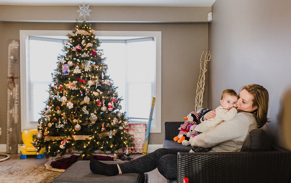 mommy and baby girl in front of christmas tree