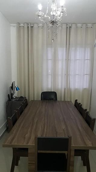 Sala de reunião com lustre de cristal computador e mesa com seis cadeiras