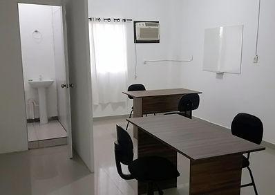 Sala mobiliada com duas mesas de atendimento e quatro cadeiras, arcondicionado, quadro branco e banheiro privativo