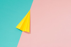 Yellow paper airplane on pastel pink and