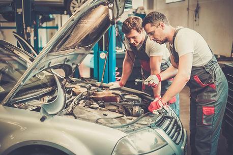 auto mechanics in auto repair shop working on car engine