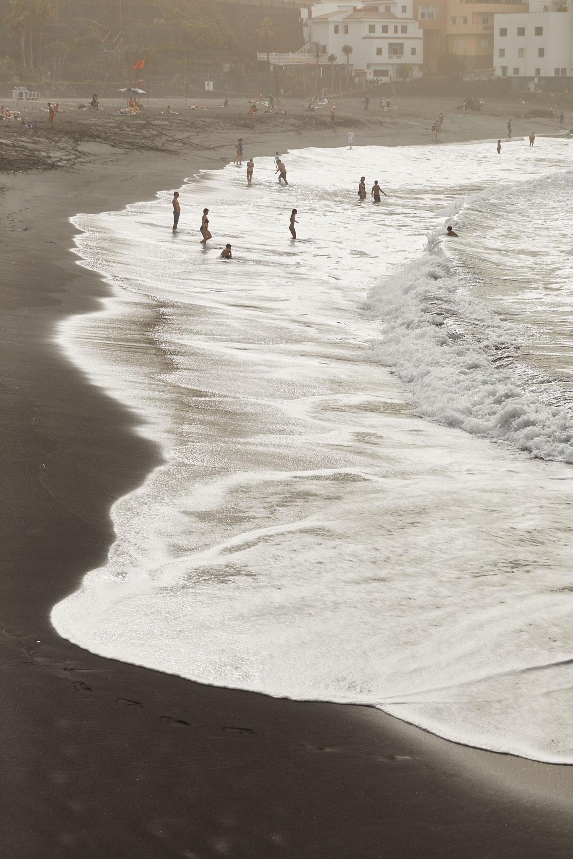 photographe outdoor en voyage sur une plage de sable noire à tenerife