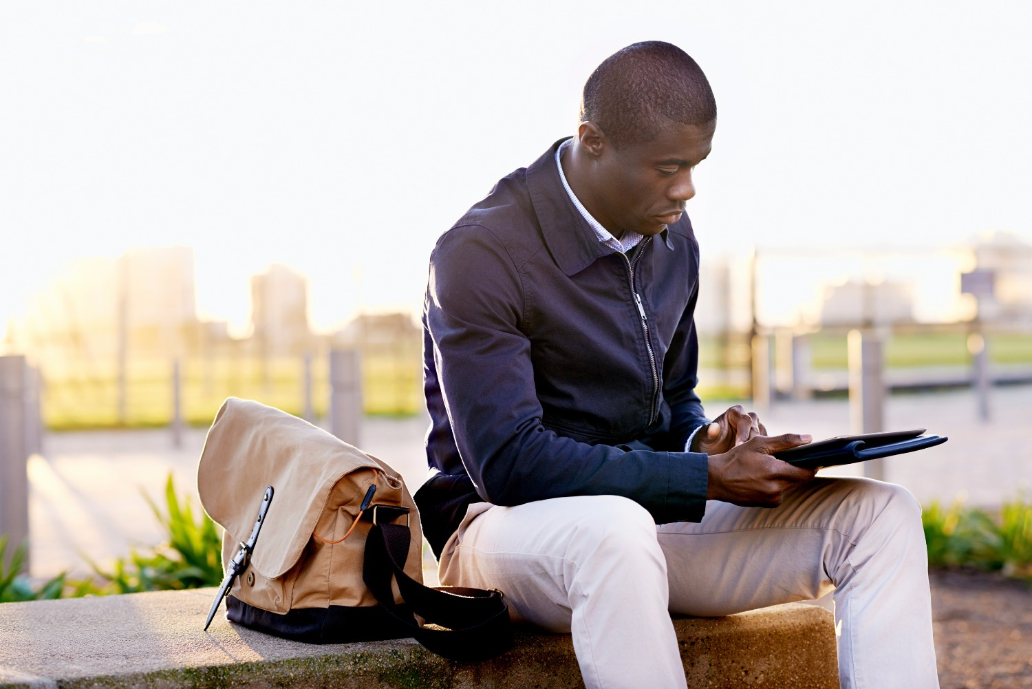 African black business man hipster using tablet computer in park on break from work_edited