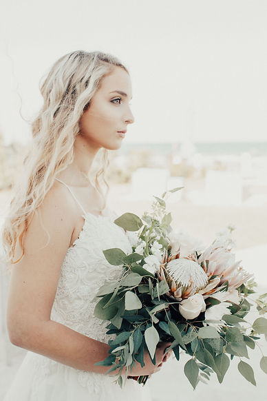 Bride at The Salty Mermaid beach holding bouquet