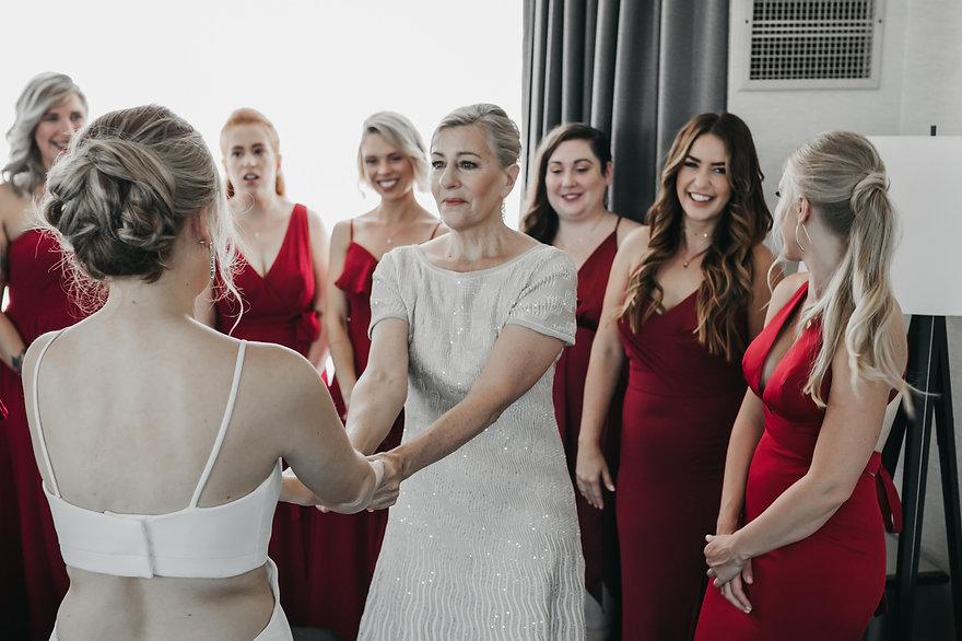 bride's mother looking at bride in wedding dress