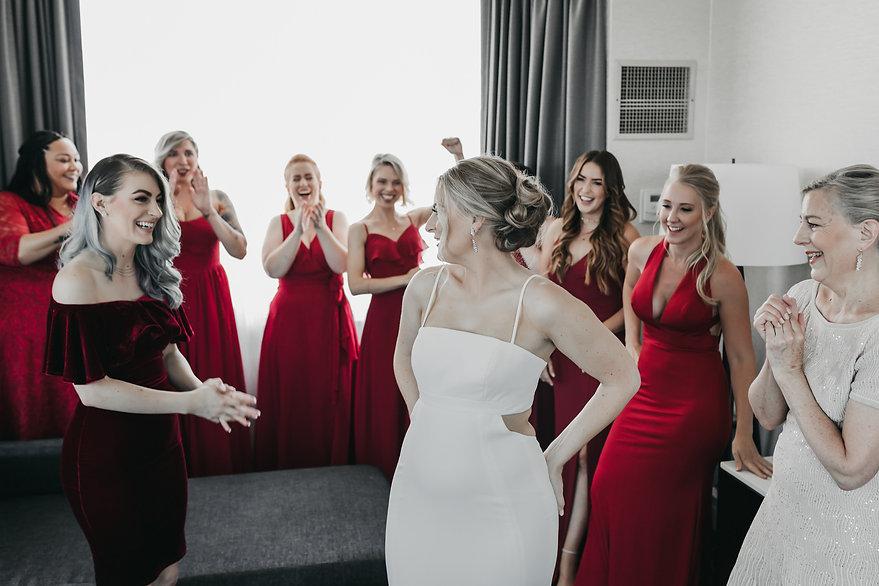 bridesmaid cheering on bride in wedding dress