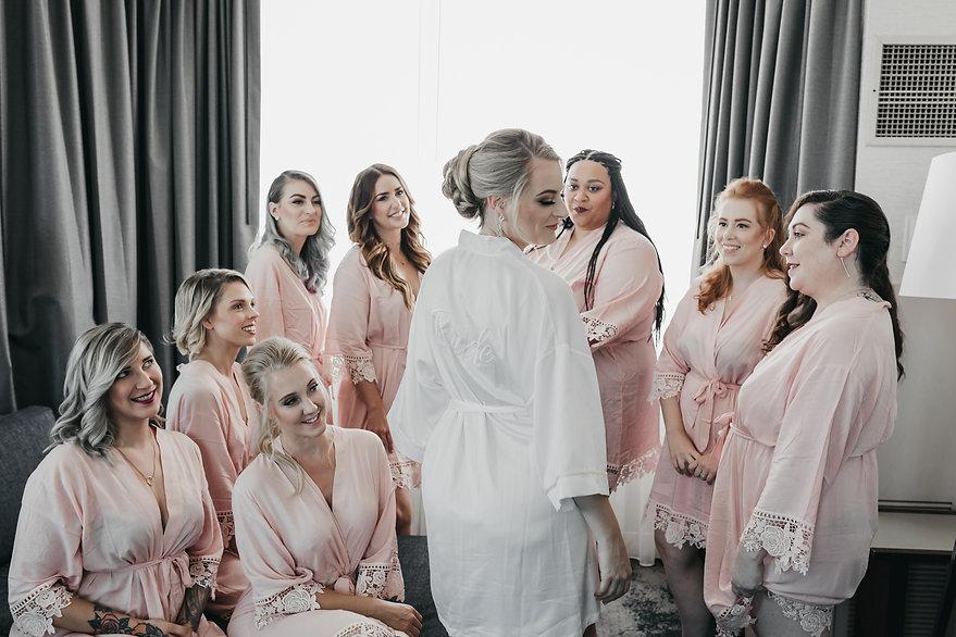 bride in robe with bridesmaids