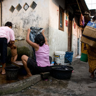 Women are bathing child and washing clothes in the street, Senen