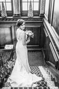 Bride walking down the stairs at St Giles House Norwich