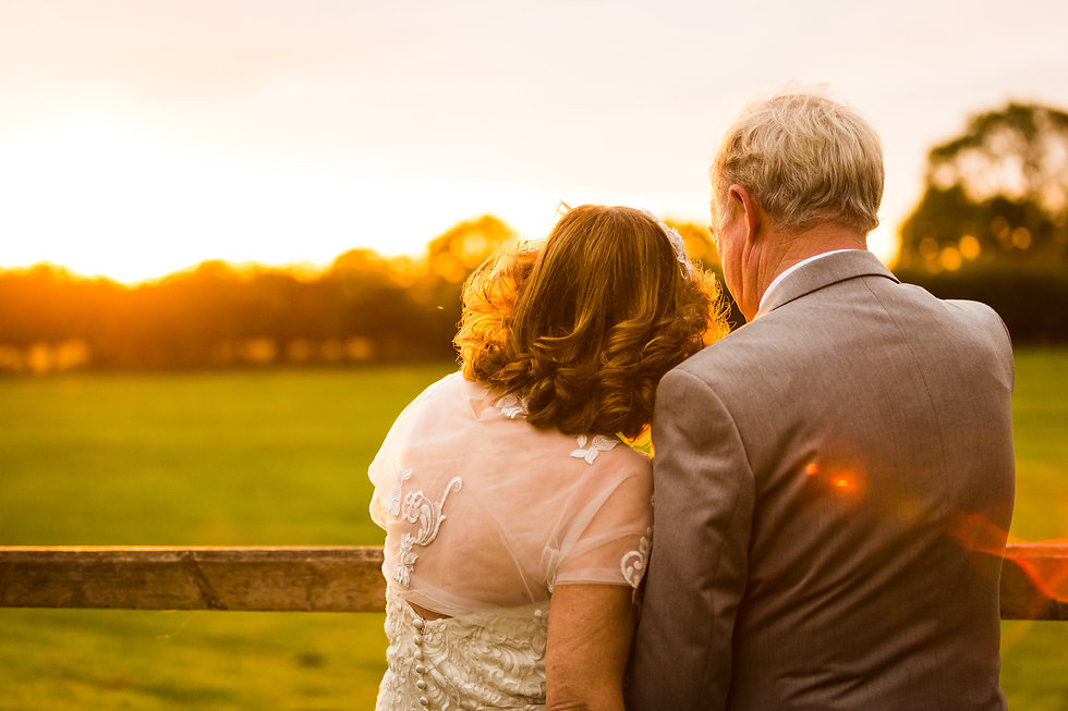 Older bride and groom looking into the sunset