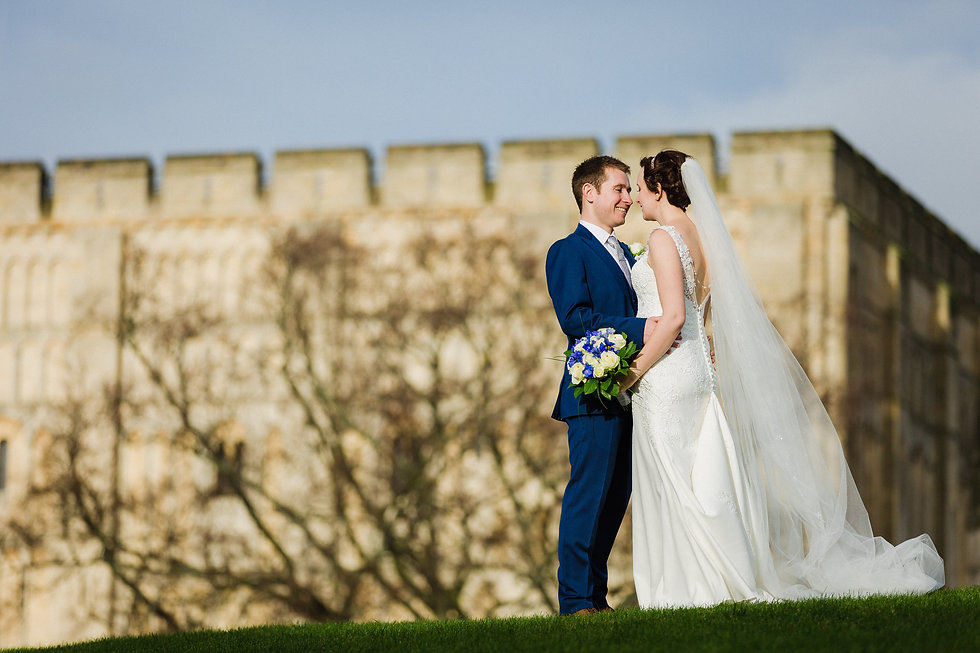 Bride and groom looking lovingly at Norwich Castle