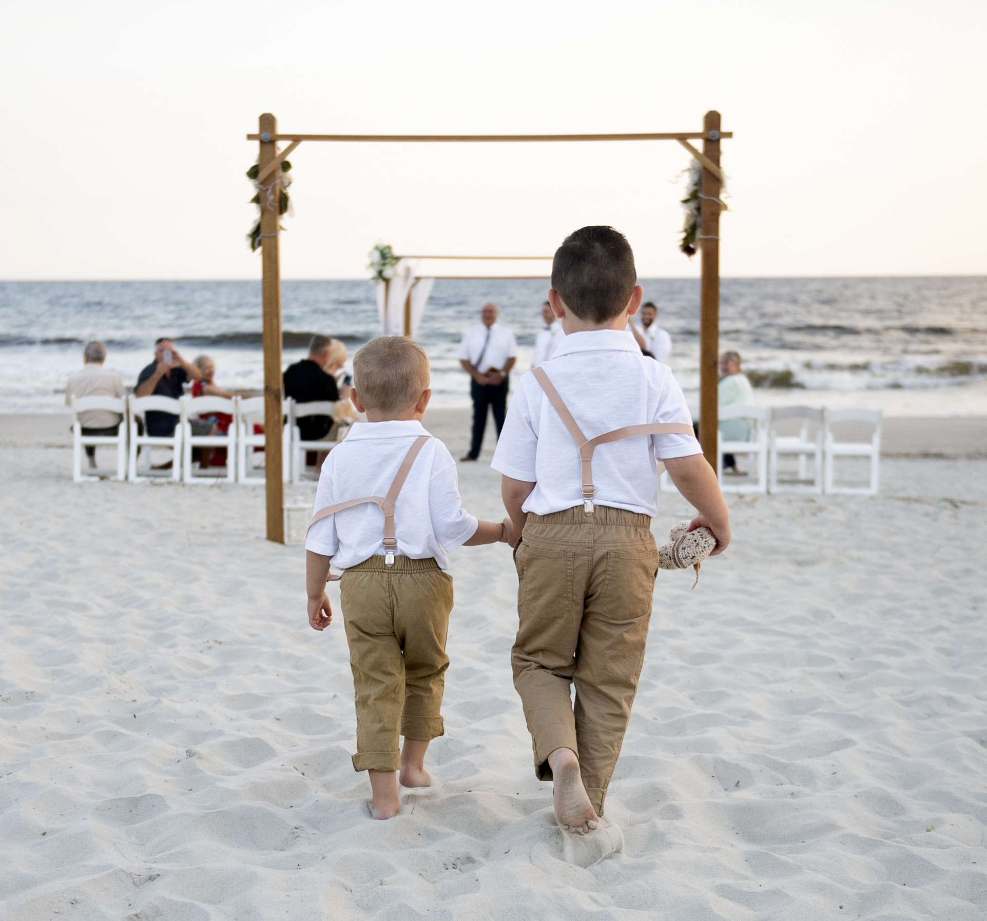 Frank Hart Photography Ocean Isle Inn wedding at Ocean Isle Beach. Ring bearers walk down the aisle.