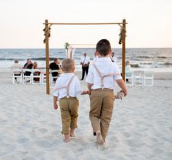 Frank Hart Photography shoots Ocean Isle Inn wedding at Ocean Isle Beach. Ring bearers walk down the