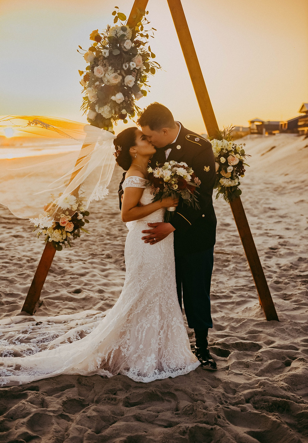 Bride and Groom kissing on beach at sunset after their oak island wedding at the beach