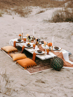 boho wedding table scape with pillow seating and vintage thrift store glassware