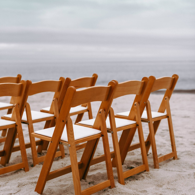 natural wood folding chairs beach wedding ceremony Oak Island wedding Blue Satin Bee