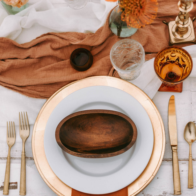 boho place setting with gold flatware and wooden bowl vintage glassware for a boho wedding at Oak Island, NC